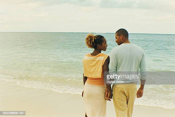 Couple holding hands on beach, rear view