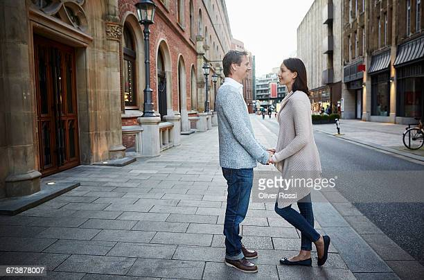 couple holding hands on city street - cardigan sweater stock pictures, royalty-free photos & images