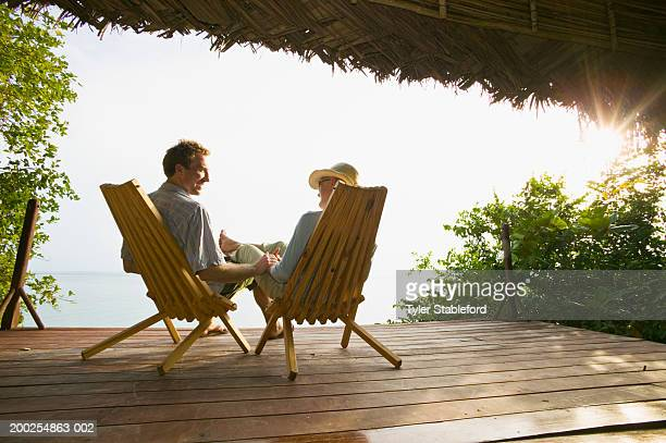 Couple holding hands on deck of thatch roofed bungalow, rear view, sun