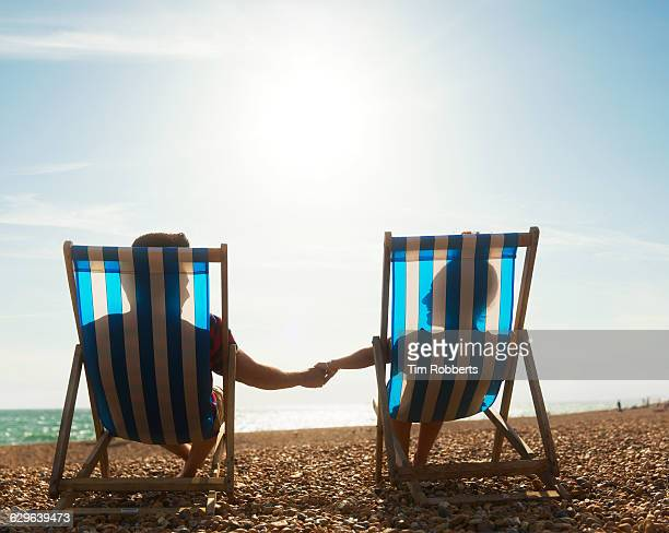 Couple holding hands on deckchairs