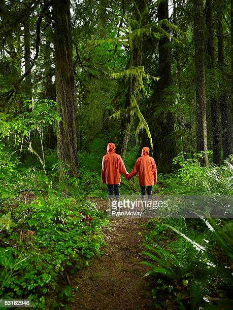 Couple holding hands on forest trail.