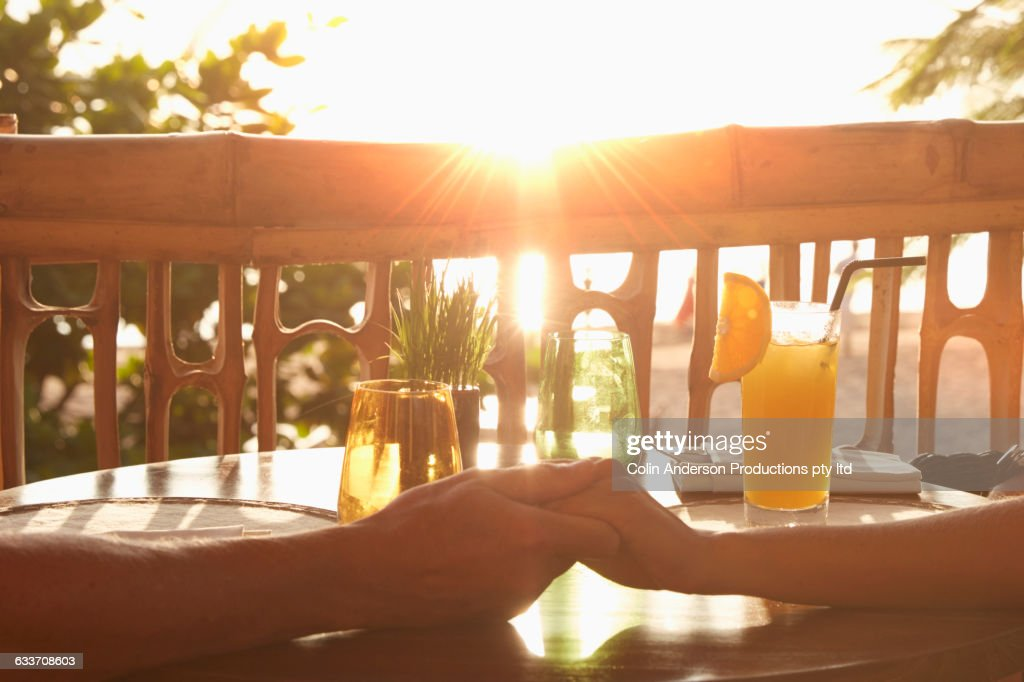 Couple holding hands on patio : Stock Photo
