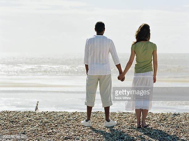 Couple holding hands on pebble beach, facing ocean, rear view