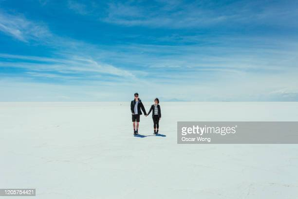 couple holding hands on salt flat, salar de uyuni - ウユニ ストックフォトと画像