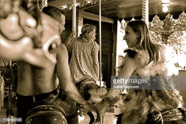 Couple holding hands on the carousel, and a single woman with a wreath of flowers in her hair gazing out at the crowd at the 1st Elysian Park Love-In...