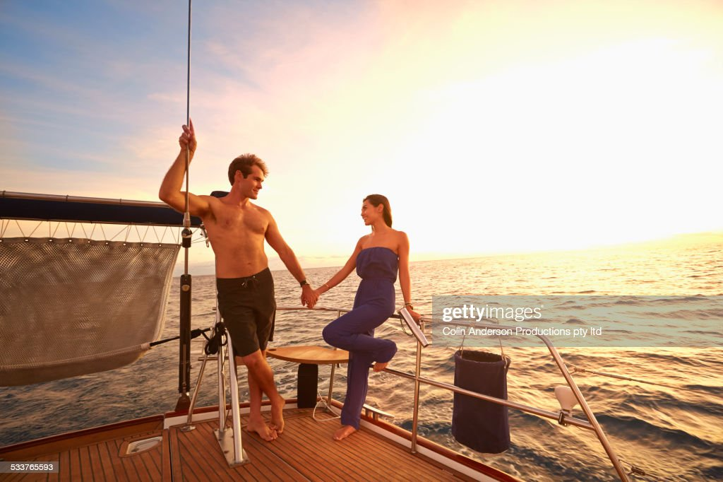Couple holding hands on yacht deck : Foto stock