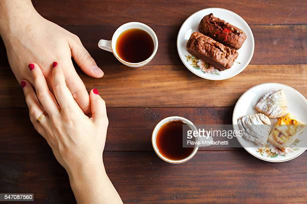 Couple holding hands over coffee table
