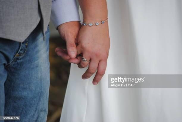couple holding hands - braccialetto foto e immagini stock