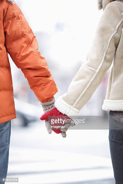 couple holding hands - beige glove stock photos and pictures