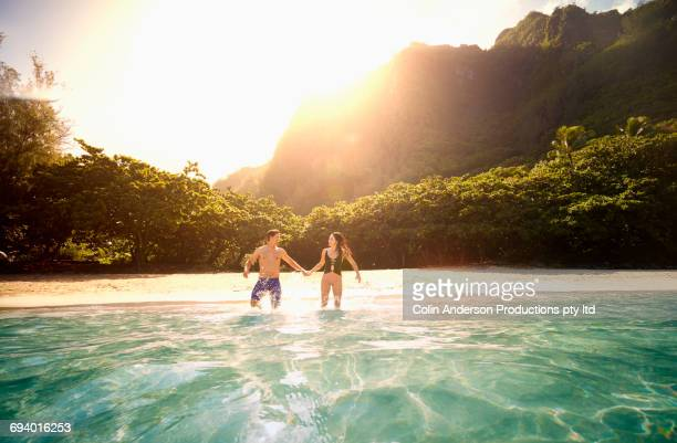 couple holding hands running into ocean - beach holiday stock pictures, royalty-free photos & images