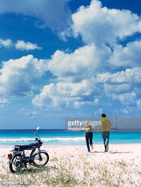 couple holding hands running towards ocean, motorbike in foreground, rear view - blasius erlinger stock pictures, royalty-free photos & images