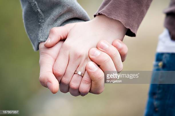Couple holding hands showing that they just got engaged
