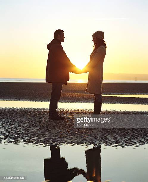 couple holding hands, standing on beach facing each other, dawn - coat stock pictures, royalty-free photos & images