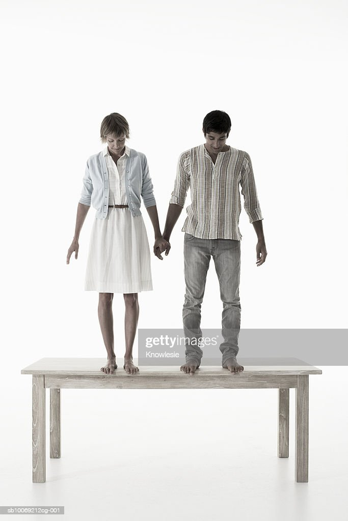 Couple holding hands standing on wooden table against white background : Stockfoto