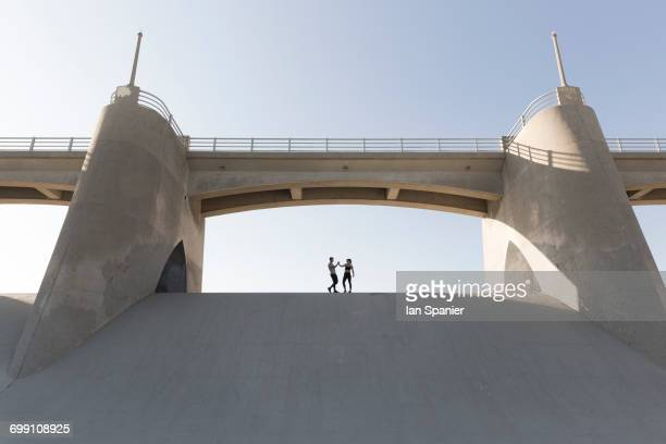 'Couple holding hands under bridge, Van Nuys, California, USA'