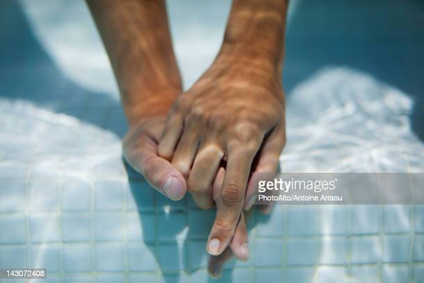 Couple holding hands underwater, cropped