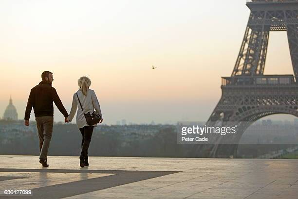 couple holding hands, view of eiffel tower - twilight stock pictures, royalty-free photos & images