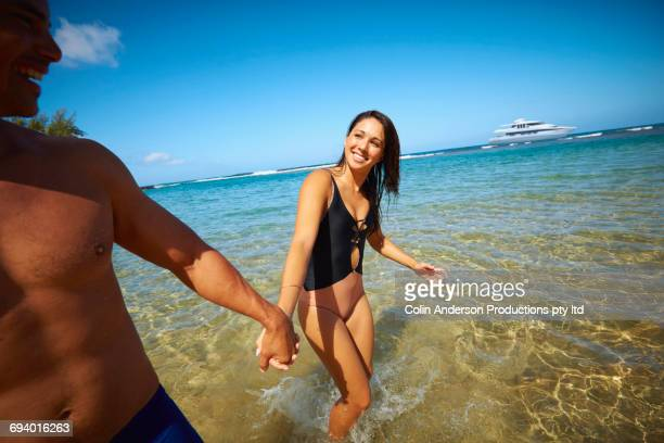 couple holding hands wading in ocean - gleichheit stock-fotos und bilder