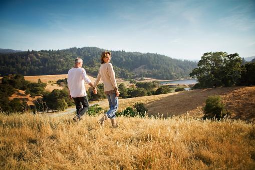 Couple holding hands walking in field - gettyimageskorea