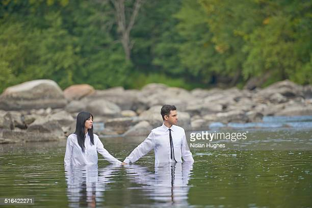 couple holding hands walking in water - waist deep in water stock pictures, royalty-free photos & images