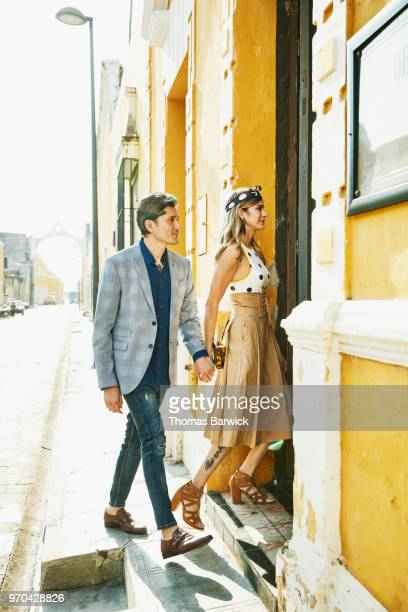 Couple holding hands walking into hotel after exploring town during vacation