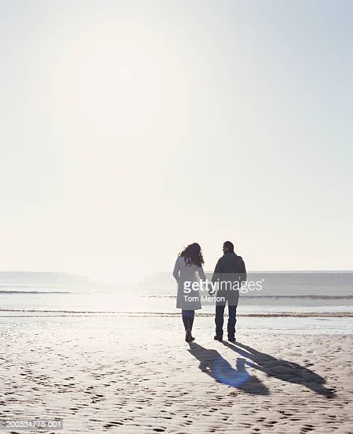 Couple holding hands, walking on beach, rear view (sun flare)
