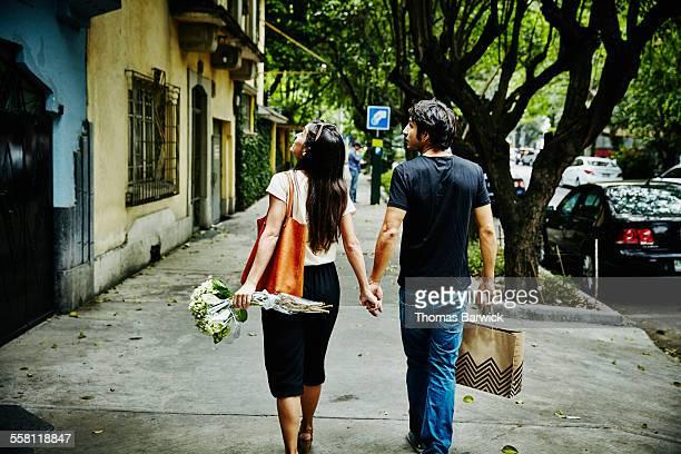 Couple holding hands walking on sidewalk