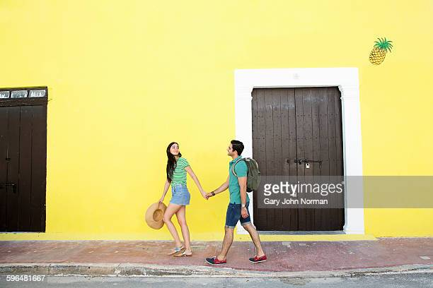 Couple holding hands walking past yellow wall.
