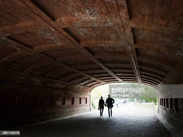 Couple holding hands walking through a tunnel in Central park, Manhattan.
