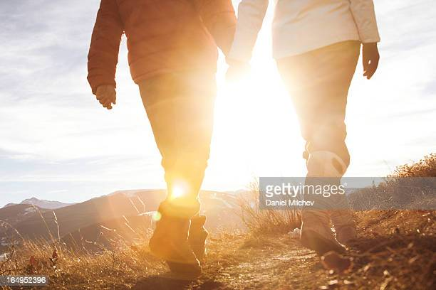 Couple holding hands, walking towards the sun.