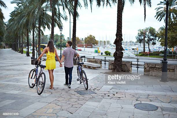 couple holding hands & walking with bicycles - klaus vedfelt mallorca stock pictures, royalty-free photos & images