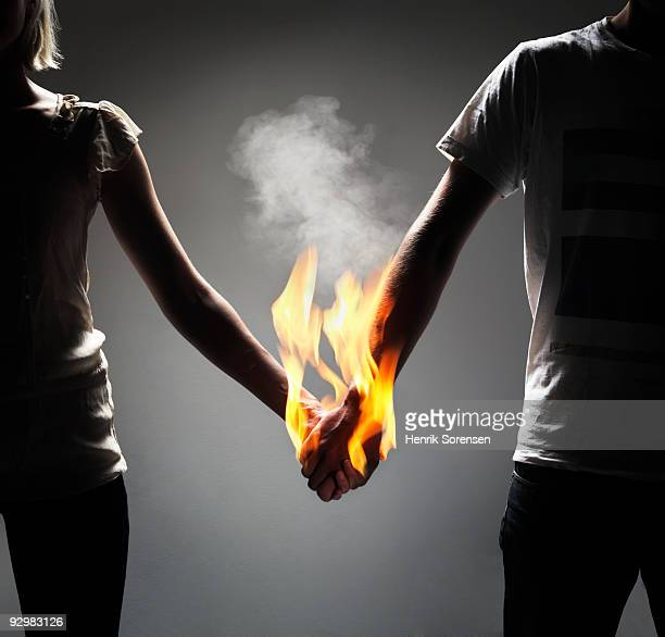 Couple holding hands which are engulfed in flames