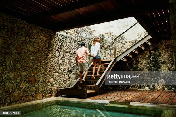 Couple holding hands while ascending stairs to room at luxury resort