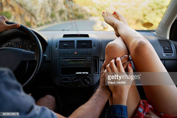 couple holding hands while driving car - berühren stock-fotos und bilder