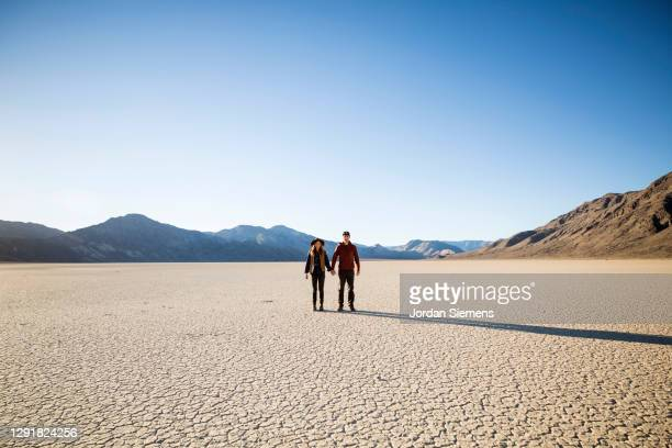 a couple holding hands while hiking in the racetracks region of death valley - nevada stock-fotos und bilder