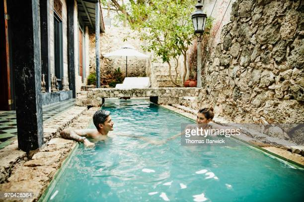 Couple holding hands while relaxing in courtyard pool of spa