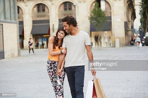 Couple holding hands while walking in city