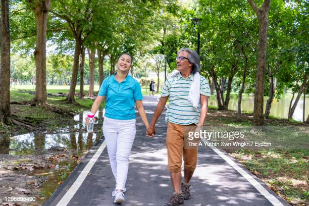 couple holding hands while walking on road against trees in park - affectionate stock pictures, royalty-free photos & images