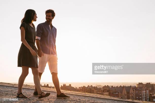 couple holding hands while walking on road during sunset - erwachsener über 30 stock-fotos und bilder