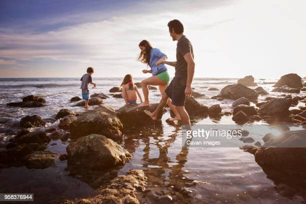 couple holding hands while walking with playful children at beach - cuatro personas fotografías e imágenes de stock