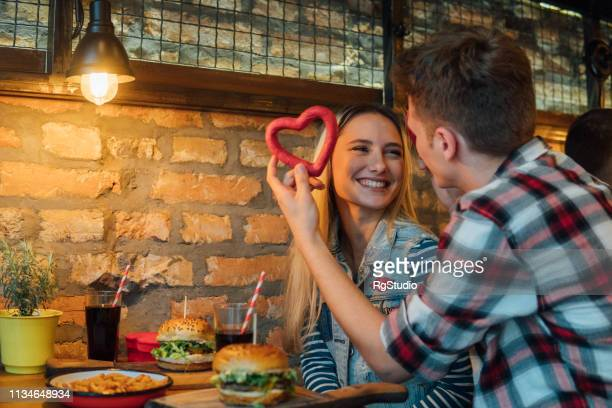 couple holding heart shaped bagel - valentines day dinner stock pictures, royalty-free photos & images