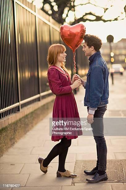 Couple holding heart-shaped balloon