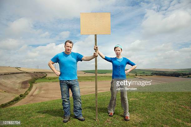 couple holding hill top protest - placard stock pictures, royalty-free photos & images