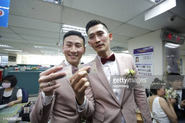 Couple holding identity cards poses for photographs while registering for marriage at a Household Registration Office in Taipei, Taiwan, on Friday,...