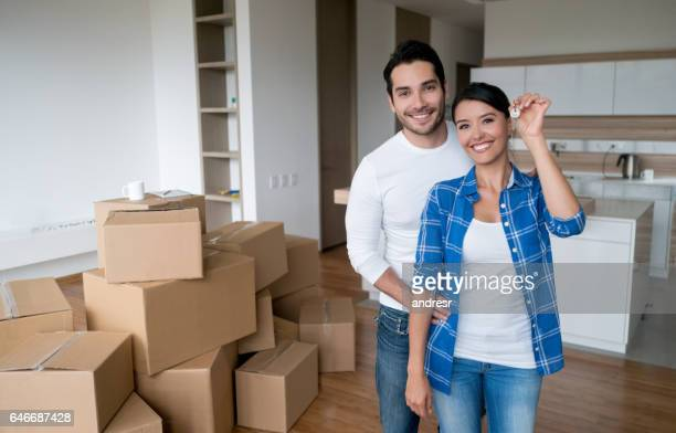 couple holding keys to their new house - house key stock photos and pictures