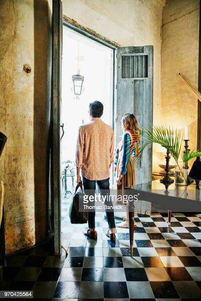 Couple holding luggage standing at doorway of boutique hotel
