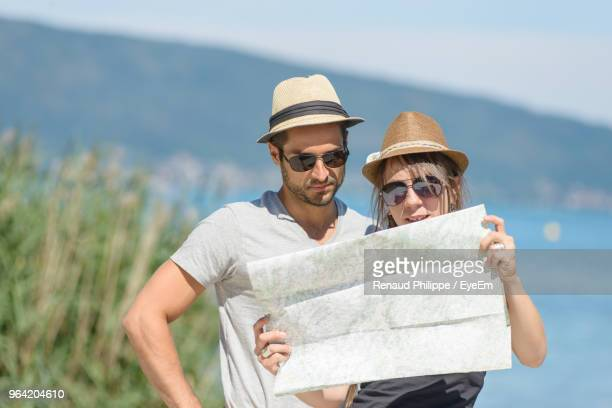 Couple Holding Map While Standing Outdoors