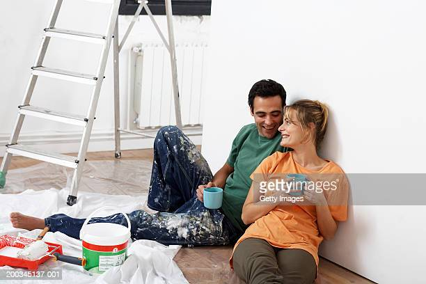 Couple holding mugs, sitting on floor by paint, smiling