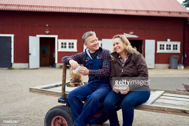 Couple holding mugs while sitting on old-fashioned trailer against barn