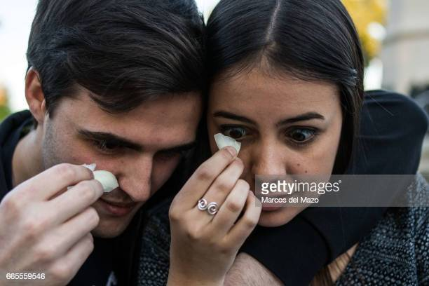 A couple holding onions near their eyes trying to cry during an event organized through Facebook under the name 'Gathering for crying' celebrated in...